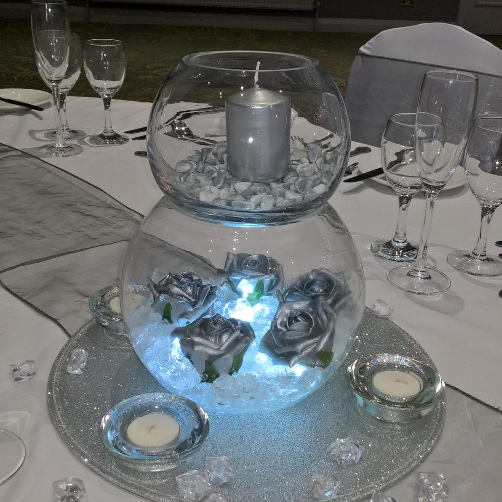 Double goldfish bowl wedding centrepiece with flowers and lights