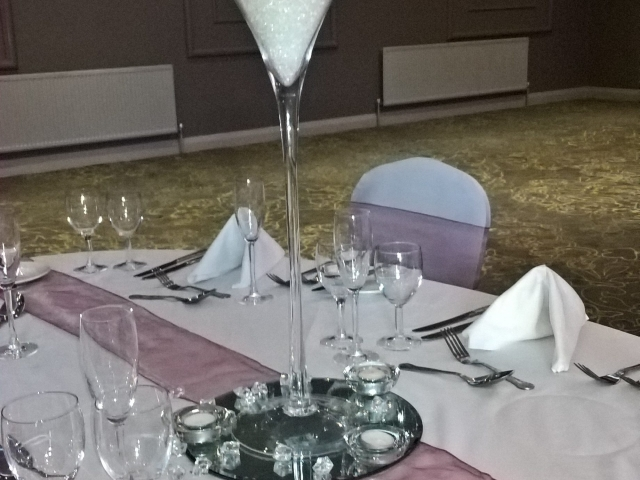 Tall martini glass filled with stones and flowers