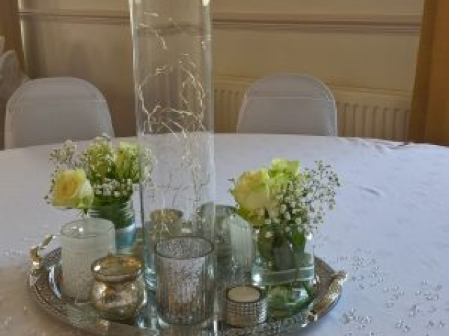 Table centrepiece with cylindrical vase, lights and jars on silver tray