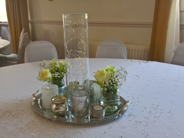 Silver coloured platter with large vase and lights, tealights and flower filled vases