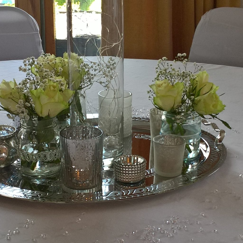 Centrepiece with cylindrical vase, jars and candles on silver tray