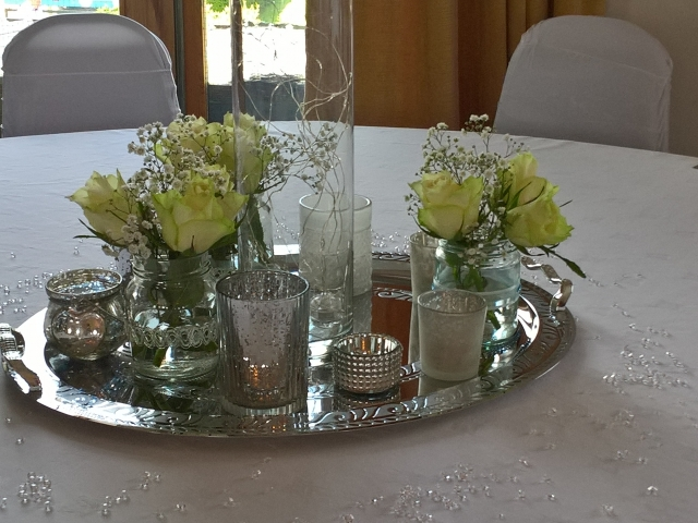 Silver coloured platter with vases, tealights and roses