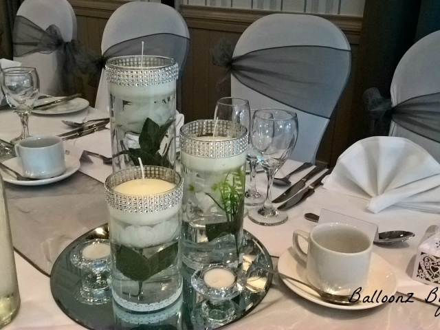 Three vases with diamante trim white flowers, floating candles