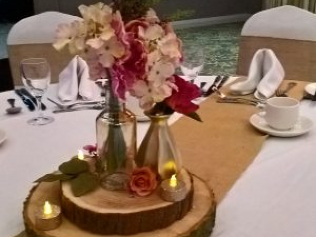 Rustic style wedding centrepiece - logs and vases