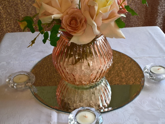 Rose gold coloured glass filled with roses