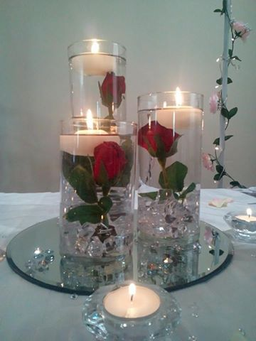 Three vases with roses and floating candle